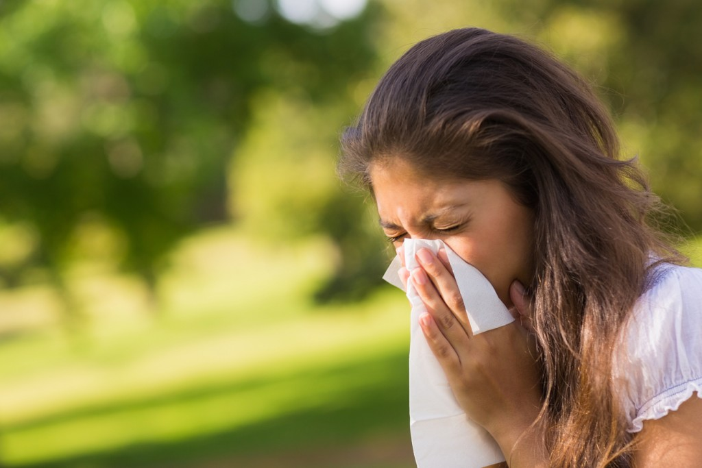A woman is blowing her nose outside due to her allergies.