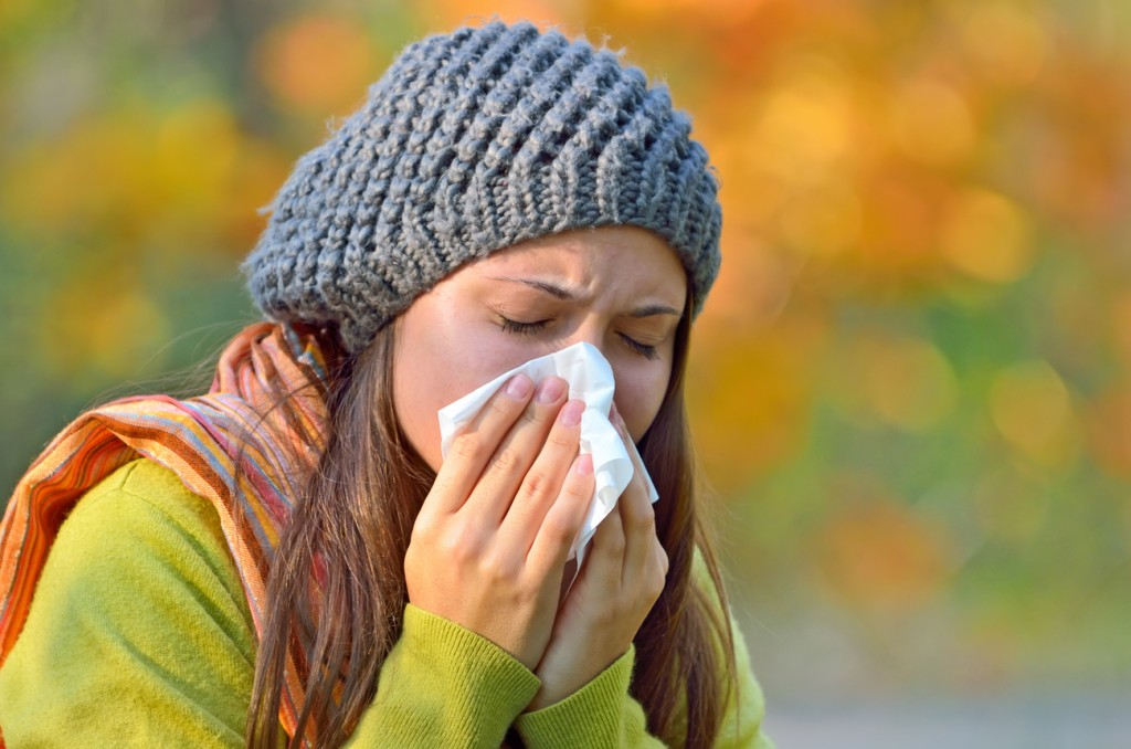 A girl sneezing into a tissue because of sinusitis.