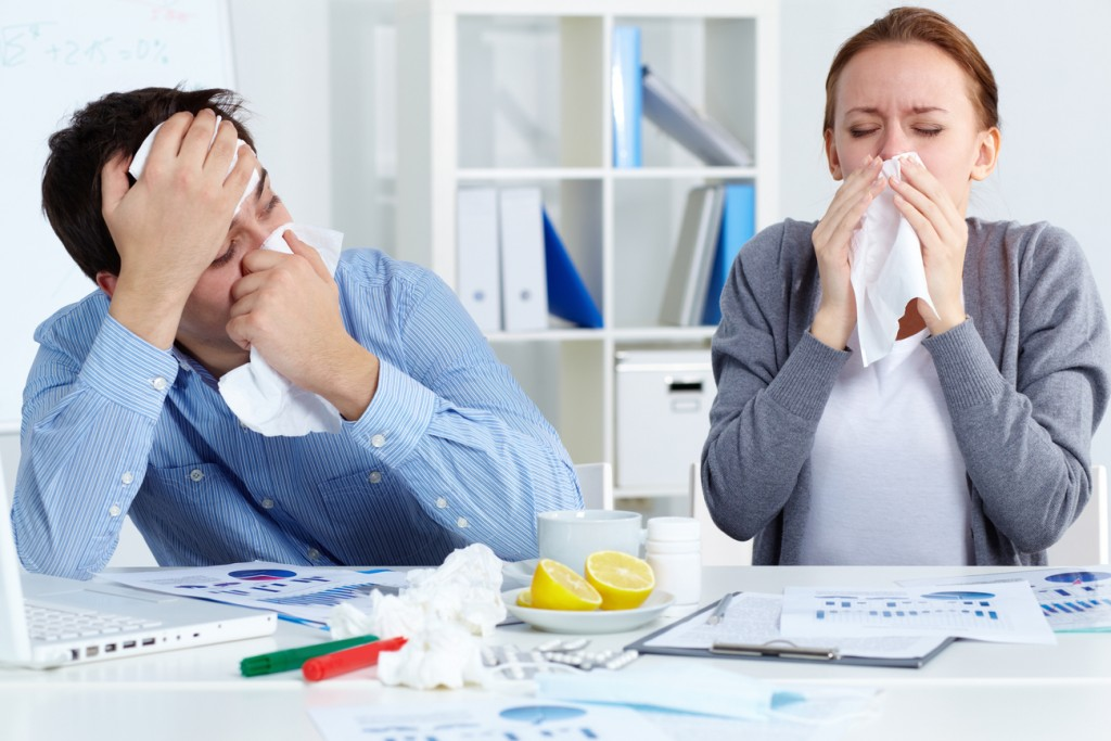 An image of two sick co-workers who didn't take precautions to prevent sinusitis. They are both blowing their nose into tissues.