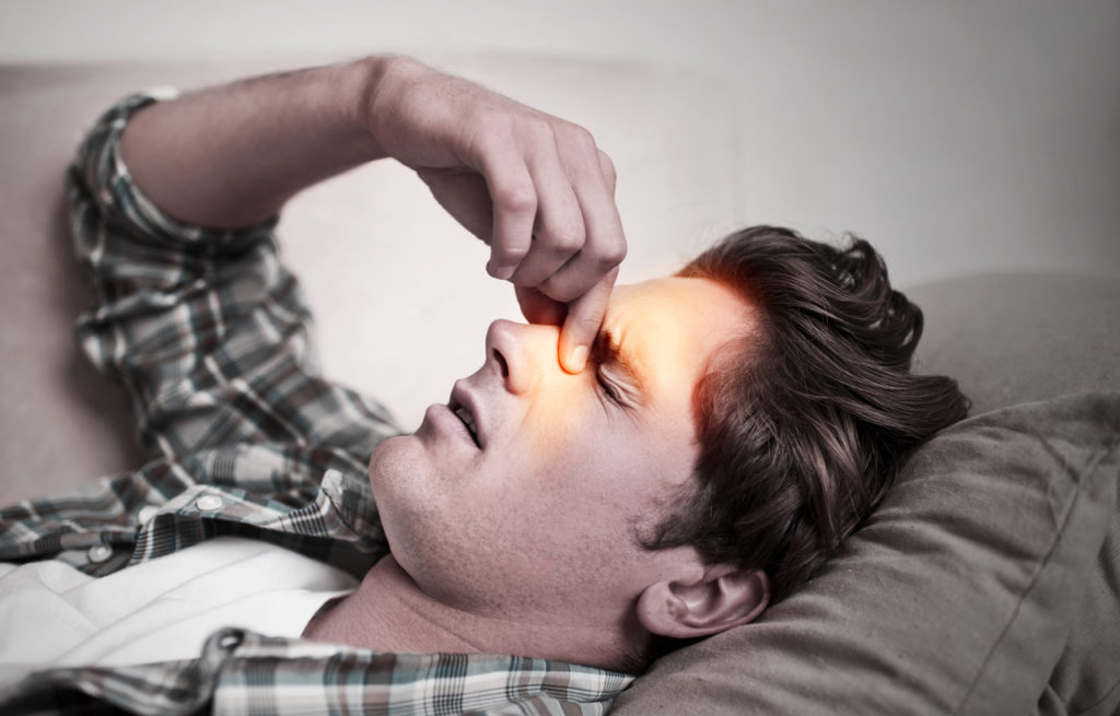 A young man holds his nose in pain due to sinusitis, which can be worsened by obesity.