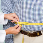 A doctor measures an overweight man's waist. Obesity and sinusitis, when both present, can create a negative spiral of symptoms.
