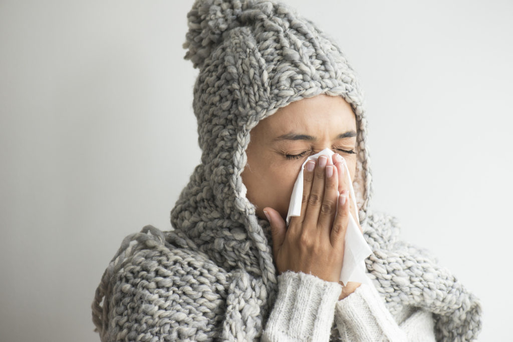 A woman dressed in a thick sweater and beanie sneezes into a tissue. Viral sinus infections can be contagious.
