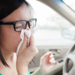 A woman is holding a tissue to her nose, sitting in her car. Depending on what the cause of her sinus infection was, it may or may not be contagious.
