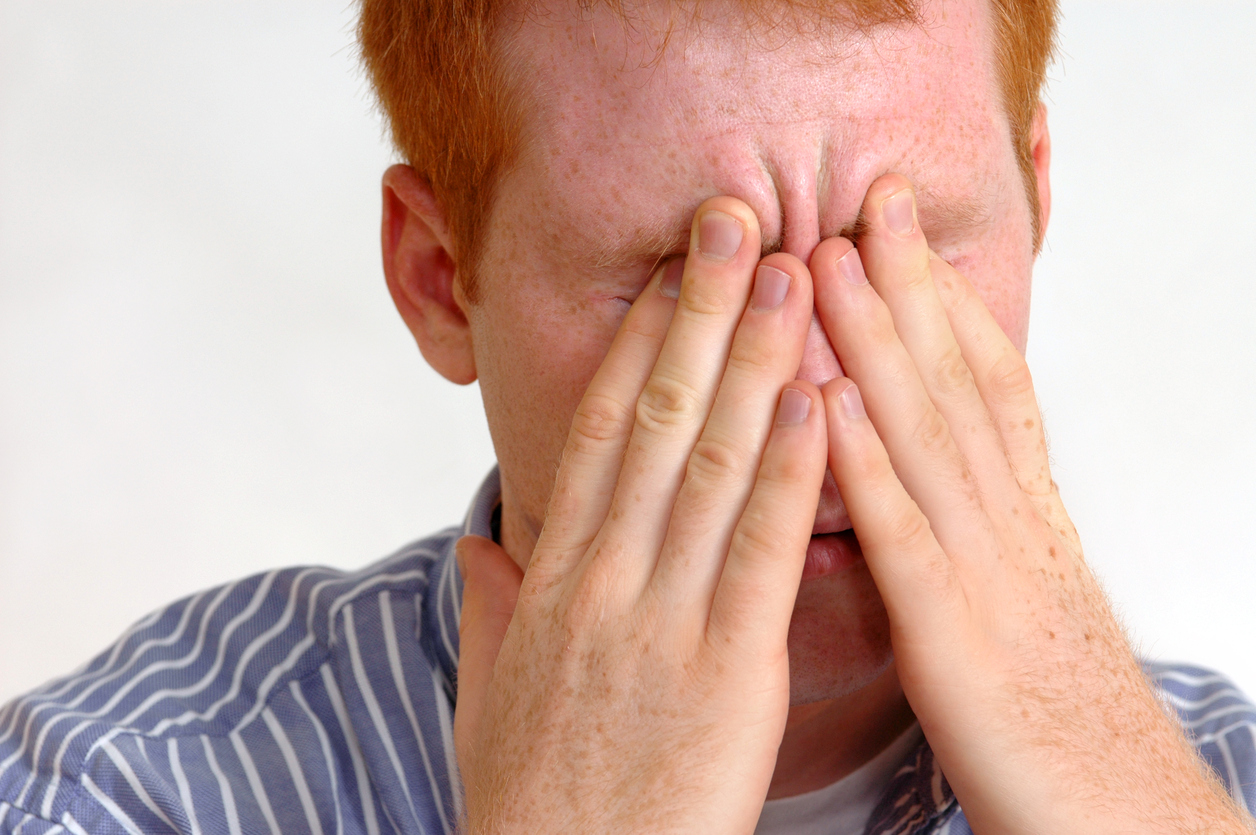 A man holds his nose in pain, since he suffers from sinus thrombosis.