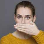 A young woman suffers from sinusitis and halitosis.