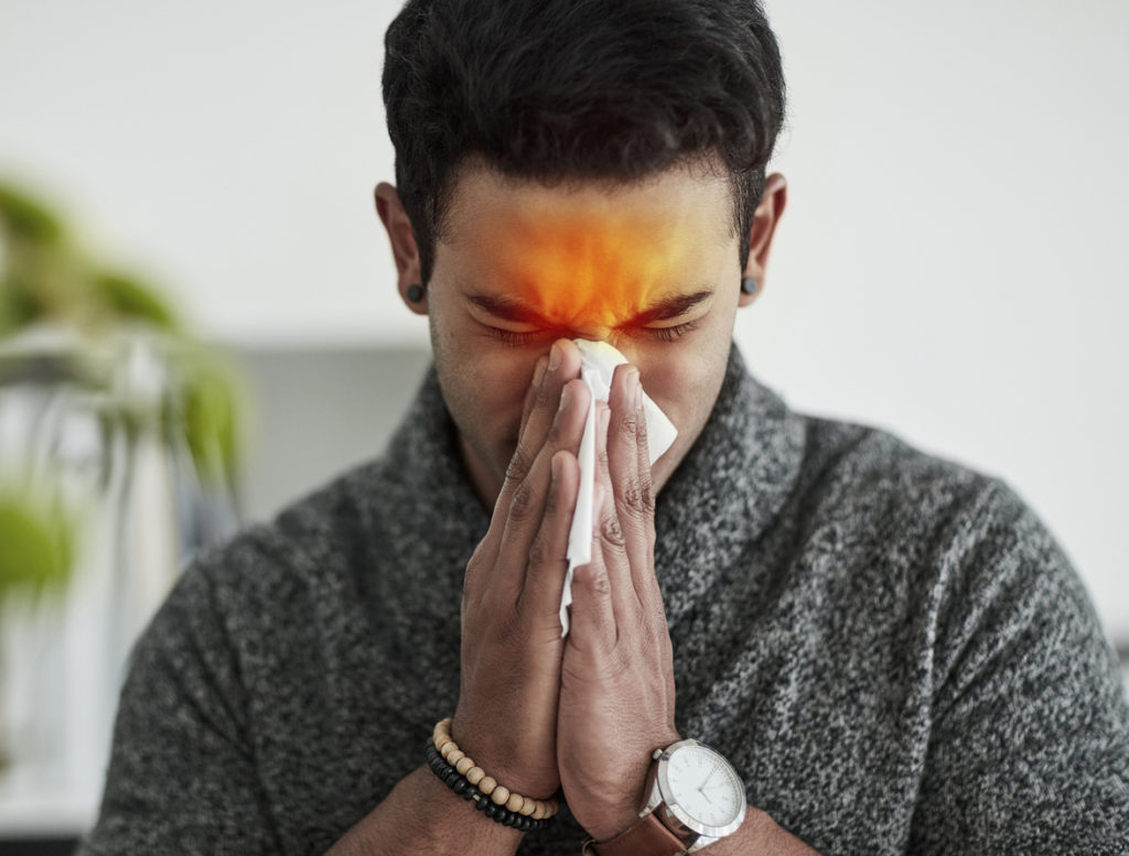 A man sneezing into a tissue who needs photodisinfection treatment.