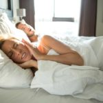A woman has her sleep interrupted by her spouse who requires treatment to prevent snoring issues.