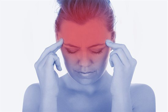 A woman presses on her head in severe pain and thinks about talking to her doctor to confirm she is a good candidate for balloon sinuplasty treatment.